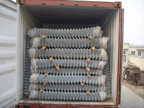 Chain link mesh rolls in container with wooden sticks between two layers.